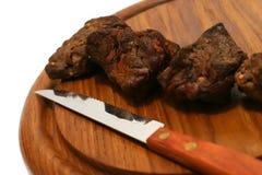 Carne en la placa con el cuchillo Fotografía de archivo