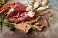 Carne escura fresca com os ingredientes para cozinhar na placa de corte de madeira marrom fotos de stock