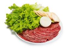 Carne fino cortada fresca cruda con lechuga Fotos de archivo