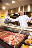 Carne fresca com carniceiro alegre Imagens de Stock