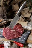 Carne fresca com a faca em cortar a placa preta, ainda vida dentro Imagens de Stock Royalty Free