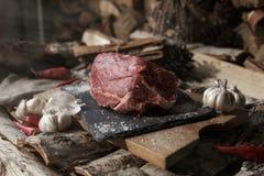 Carne fresca com a faca em cortar a placa preta, ainda vida dentro Fotos de Stock