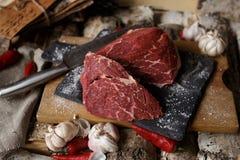 Carne fresca con el cuchillo en cortar el tablero negro, aún vida adentro Imagen de archivo