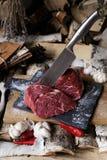 Carne fresca con el cuchillo en cortar el tablero negro, aún vida adentro Fotos de archivo
