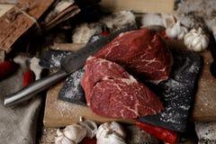 Carne fresca con el cuchillo en cortar el tablero negro, aún vida adentro Fotos de archivo libres de regalías