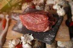 Carne fresca con el cuchillo en cortar el tablero negro, aún vida adentro Imagenes de archivo