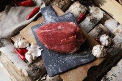 Carne fresca con el cuchillo en cortar el tablero negro, aún vida adentro Imágenes de archivo libres de regalías