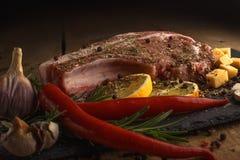 Carne fresca con los ingredientes para cocinar en el fondo de madera imagen de archivo