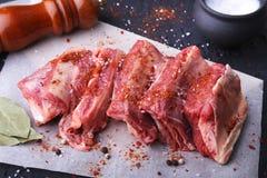 Carne fresca cruda, costole crude di manzo o dell'agnello con pepe, aglio, sale, le foglie della baia e le spezie su fondo di pie fotografie stock