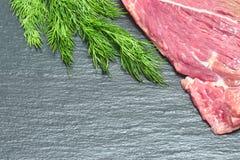 Carne fresca cruda del manzo su un fondo nero con un ramoscello di aneto immagini stock