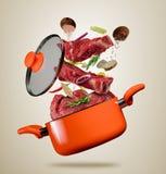 Carne fresca da carne e voo da carne em um potenciômetro no fundo cinzento Fotos de Stock Royalty Free