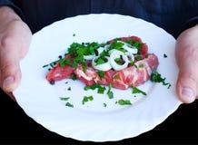 Carne fresca decorada com verdes na placa branca Fotografia de Stock Royalty Free