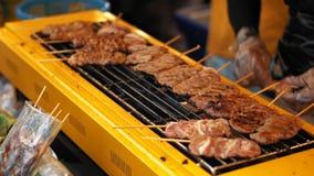 Carne fresca suculenta em espetos de madeira em uma grade quente, movimento lento O assado delicioso é fritado no exterior filme