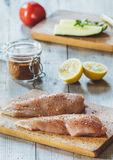 Carne fresca sul bordo di legno con la spezia, il pomodoro ed il limone sulla tavola Immagine Stock