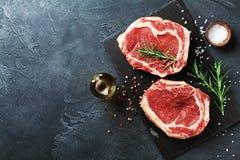 Carne fresca sul punto di vista superiore del bordo del nero dell'ardesia Bistecca e spezie di manzo crude per cucinare fotografie stock libere da diritti