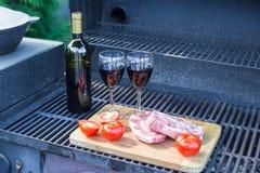 Carne fresca, verduras y botella de vino en una comida campestre al aire libre Fotografía de archivo