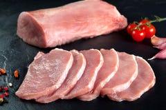 Carne fresca y cruda Filete de cerdo, filetes de los medallones del lomo en fila listos para guisar Pizarra negra del fondo Imagen de archivo libre de regalías