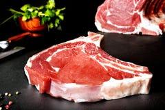 Carne fresca y cruda Ribeye Los filetes crudos asaron a la parrilla el Bbq en la pizarra negra del fondo Foto de archivo libre de regalías