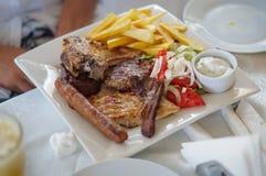 Carne frita con las patatas fritas en una placa en un restaurante Imagen de archivo libre de regalías