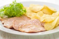 Carne frita con las patatas fritas y la ensalada fresca en el plato blanco Foto de archivo libre de regalías