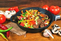 Carne frita con las verduras en una sartén del arrabio  Foto de archivo libre de regalías