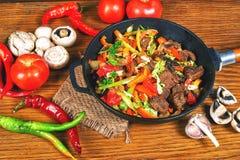 Carne frita con las verduras en una sartén del arrabio  Foto de archivo
