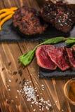Carne frita cortada, hamburguesas y participaciones En un vector de madera imagen de archivo libre de regalías