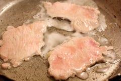 Carne frita en una sartén imagenes de archivo