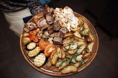 Carne frita y verduras cocidas en un tablero de madera en las manos de un camarero foto de archivo libre de regalías
