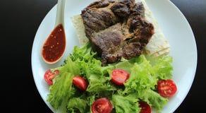 Carne fritada e molho picante servidos na placa com folhas da alface e pão fino Imagem de Stock Royalty Free