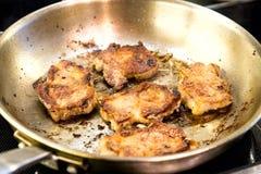 Carne fritada em uma frigideira, cozinhando Fotos de Stock