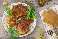 Carne fritada em uma placa com tomates e ervas, pimentas O alimento a tabela de madeira, fundo cinzento Fotos de Stock