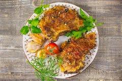 Carne fritada em uma placa com tomates e ervas, pimentas O alimento a tabela de madeira, fundo cinzento Fotos de Stock Royalty Free