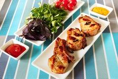 Carne fritta su un piatto bianco e su un piatto con i verdi immagini stock libere da diritti
