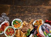 Carne gastrónoma, comidas y loza de la cena en la madera Fotografía de archivo
