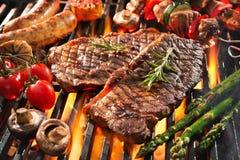 Carne grelhada deliciosa com os vegetais que chiam sobre os carvões no assado foto de stock royalty free
