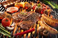 Carne grelhada deliciosa com os vegetais que chiam sobre os carvões no assado imagem de stock royalty free
