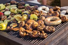 Carne grelhada deliciosa sortido com o vegetal sobre os carvões em um assado imagens de stock