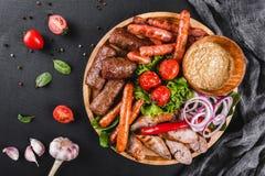 Carne grelhada deliciosa sortido e salsichas com tomates e molho do BBQ na placa de corte sobre o fundo de pedra preto Carne quen fotografia de stock