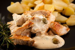 Carne grelhada do peru com molho e alcaparras de queijo na placa preta fotografia de stock royalty free