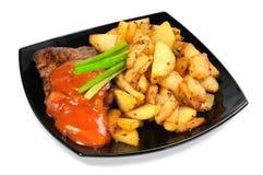 Carne grelhada e batatas fritadas em uma placa Fotos de Stock Royalty Free
