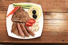 Carne grelhada em uma placa que serve a tabela de madeira rústica Imagem de Stock
