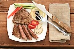 Carne grelhada em uma placa que serve a tabela de madeira rústica Foto de Stock