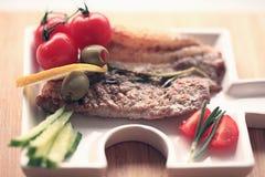 Carne grelhada em uma placa que serve a tabela de madeira rústica Imagens de Stock