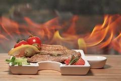 Carne grelhada em uma placa que serve a tabela de madeira rústica Imagens de Stock Royalty Free