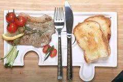 Carne grelhada em uma placa que serve a tabela de madeira rústica Fotos de Stock Royalty Free