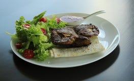A carne grelhada serviu com verdes e pão do pitta na placa branca no restaurante Imagens de Stock Royalty Free