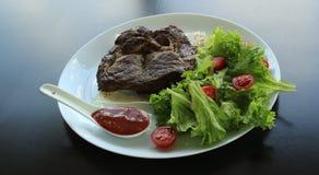A carne grelhada serviu com verdes e pão do pitta na placa branca no restaurante Fotografia de Stock Royalty Free