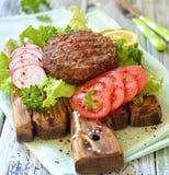 A carne grelhou o hamburguer em uma placa de madeira com vegetais Imagens de Stock Royalty Free