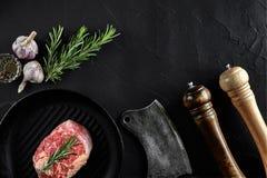 Carne grezza fresca Un pezzo di filetto di manzo sulla leccarda, con un'ascia di taglio, con le spezie per la cottura sulla tavol Immagine Stock